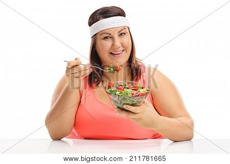 Overweight woman sitting at a table and eating a salad isolated on white background