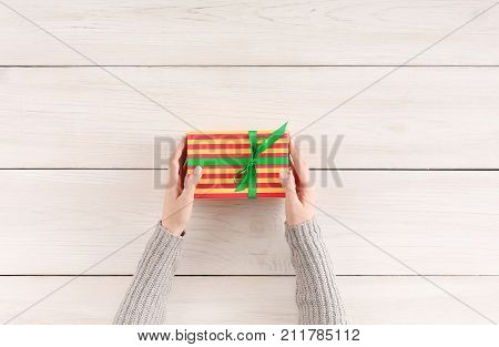 Gift wrapping background. Female hands holding handmade present box in striped paper against white wooden table background. Bithday or christmas preparation concept, top view, copy space
