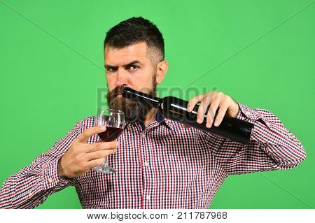 Winemaker With Strict Face Holds Wineglass And Bottle Of Wine