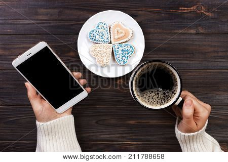 Close up of women's hands holding cell telephone with blank copy space scree for your advertising text message or promotional content hipster girl watching video on mobile phone during coffee break.