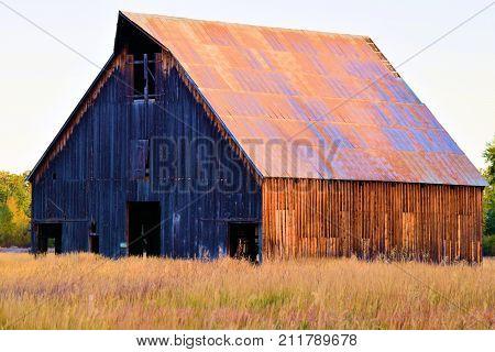 Abandoned wooden barn taken on a forgotten landscape in a rural plain