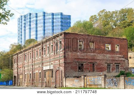 ROSTOV-ON-DON RUSSIA 07 OCTOBER 2017: Old dilapidated brick building on the street in the city of Rostov-on-Don against the background of a modern high-rise building