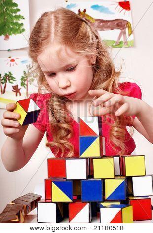 Child preschooler play block in play room. Child care.