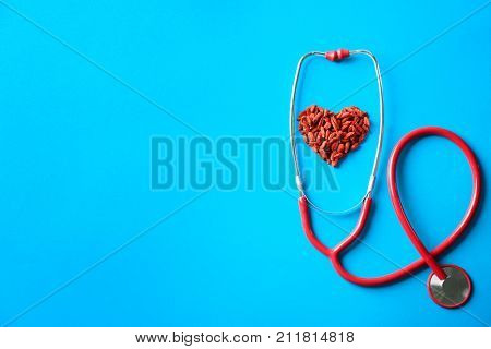 Heart made of goji berries and stethoscope on color background
