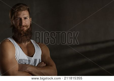 Studio portrait of a young stylish bearded man looking serious with eye contact.