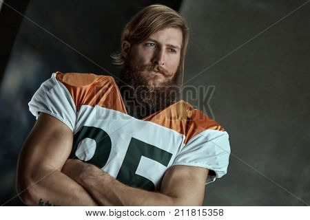Portrait of bearded american football player standing arms crossed looking away with dedication.