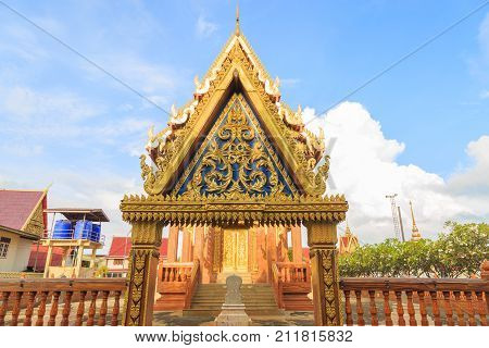 Archway church of wooden Buddhist Temple and consecrated precinct of a temple with clouds and blue sky in Thailand.