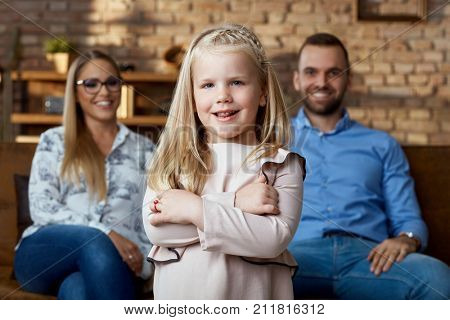 Little girl with family. Family with one child. Child standing in front, family sitting in the background.