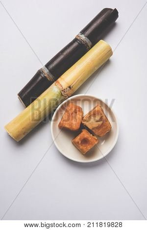 Jaggery slab, bloc and granuals with cane over white background poster