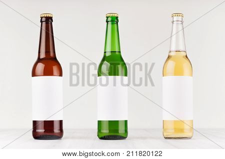 Beer bottles 500ml different colors with blank white label on white wooden board mock up. Template for advertising design branding identity.