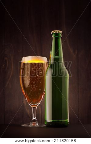 Green beer bottle and glass weizen with golden lager on dark brown wood board vertical mock up. Template for advertising design branding identity.