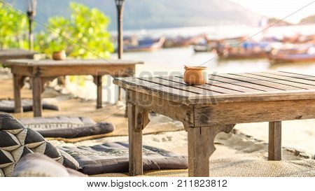 Beach and wooden decoration concept - Baked clay cup on wooden table at the beach with sunlight and copyspace use for beach travel concent