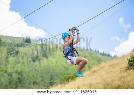 Happy smiling teen girl riding a zip line ride while on family vacation
