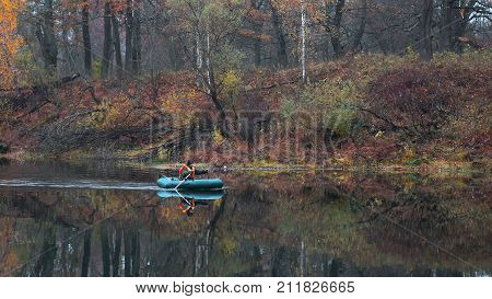 Fisherman In A Boat On The Water Of A Forest Lake In Autumn.