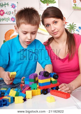 Little boy playing block with mother at home.