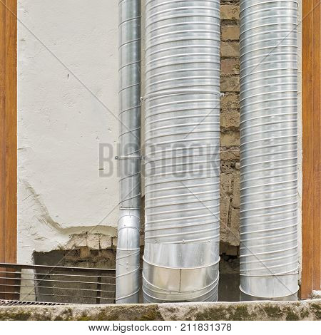 air condition metal pipes near the wall outside of the building