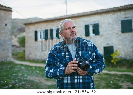 Photographer With Grey Hair In Ghost Town Old Perithia, Corfu, Greece.