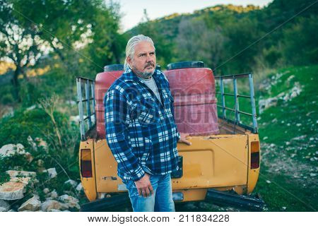 Middle Aged Man With Grey Hair And Beard At Trailer Of Vintage Pick-up Truck.