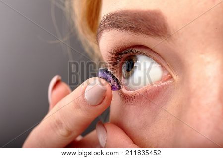 A girl with beautiful eyes inserts a colored lens close-up