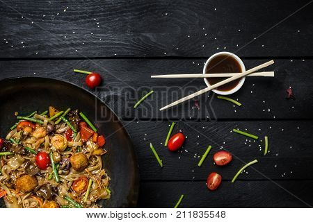 Udon stir fry noodles with seafood and vegetables in wok pan on black wooden background. With chopsticks and sauce. Top view.