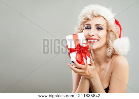 Beautiful Smiling Woman Christmas Concept. Fashion Model in Santa Hat with White Gift Box with Red Ribbon. Happy Girll with Blonde Hair Makeup and Christmas Gift