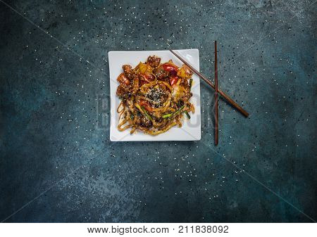 Udon stir fry noodles with meat or duck, vegetables and sesame seeds on a square white plate. With chopsticks. Top view.