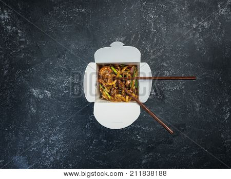Udon stir fry noodles with chicken in a box on a vintage colored background. Top view. With chopsticks.