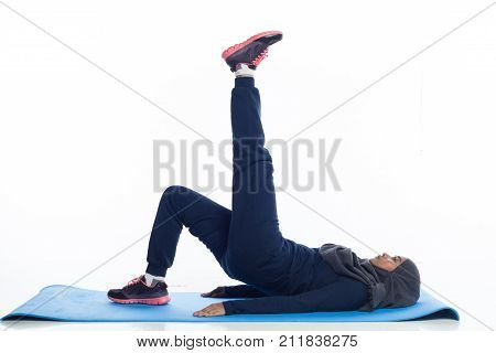 A young beautiful hijab woman is doing exercise with sport attire isolated with white background.