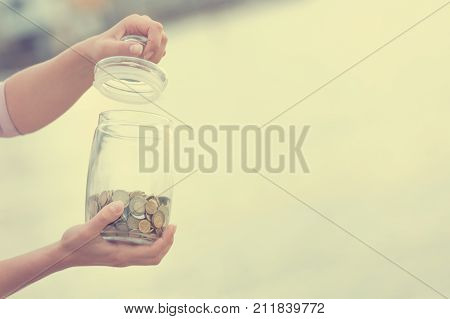 Investment retirement taxes and passive income concept. Coins in a glass jar in hand blur focus. Instagram toned on photo