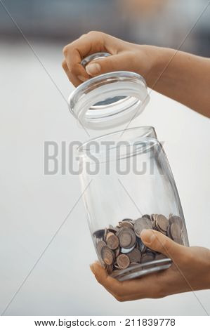 The vertical view of Investment retirement taxes and passive income concept. Coins in a glass jar in hand blur focus
