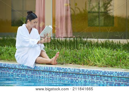Pretty young woman sitting by pool, reading a book and drinking glass of juice