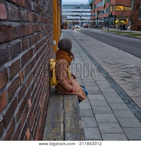 A girl with yellow backpack is waiting for a bus. Bus stop in the city. Brick walls, wooden bench. Safety, comfort. Square format