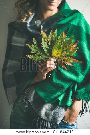 Woman in warm woolen green check scarf or blanket and jeans with Autumn fallen leaves in her hands. Fall cosy mood lifestyle concept