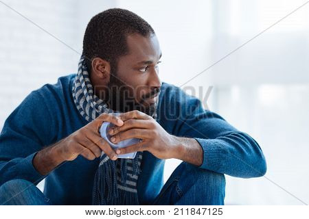 Calm man. Reliable strict thoughtful man looking to the left side while sitting quietly with a cup of tea