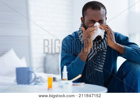 Unbearable flu. Nice young ill man sitting in his comfortable room and sneezing