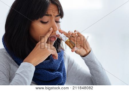 Looking careful. Young concentrated unhappy woman being very careful while using nasal drops