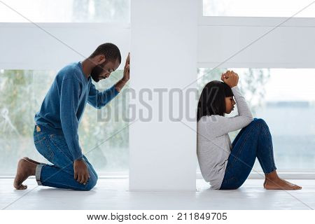 Regret. Emotional sad young man feeling sorry for offending his beautiful kind girlfriend