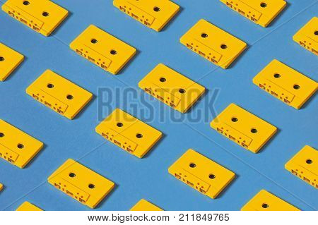 Yellow Audio Cassette Tapes On Blue Background. Creative Concept Of Retro Technology