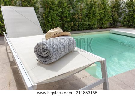 Straw hat on the sun lounger by the pool. Vacation with a tourist.