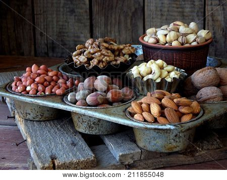 Different Varieties Of Nuts On A Wooden Background - Almonds, Cashews, Walnuts, Hazelnuts, Pistachio