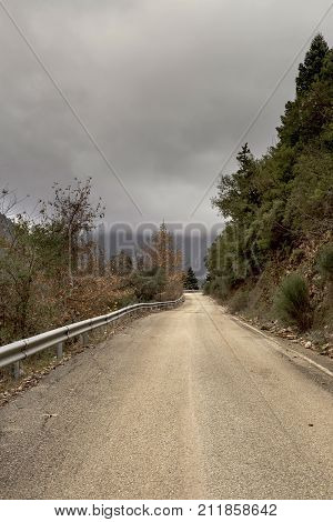 Mountain landscape. Rural road in the mountains on a cloudy, winter day (mountain Nafpaktia, western Greece)