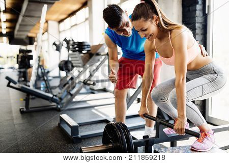 Atrractive woman doing exercises for back muscles with personal trainer in gym