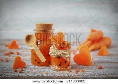 homemade carrot jam in a glass jar and decorative hearts made from fresh carrot