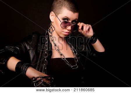 Fashion hard rock bald woman in black glasses and leather coat posing on black background