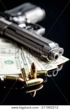 9mm bullets, american dollars and handgun.