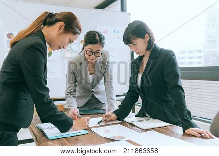 business people discussing together at conference desk and pointing report craft thinking planning during meeting in office.