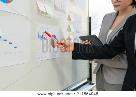 closeup photo of business team meeting with whiteboard and pointing chart document to discussion plan.