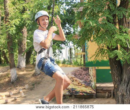 Cute boy having fun in adventure park