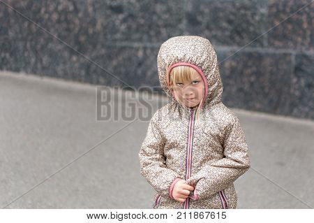 Little Cute  Caucasian Blonde Girl In A Hooded Jacket Upset Or Offended Standing Alone On A City Str