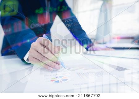 Business and finance investment concept. Businessman check about cost and doing finance graph report at office Finance managers taskBusinessman recheck new plan financial graph data.
